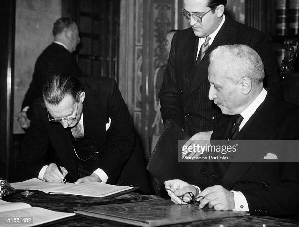 The Italian President of the Council Alcide De Gasperi countersigning the Constitution, observed by the Preident of the Italian Republic Enrico De...