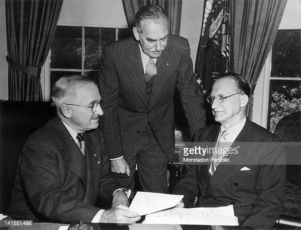 The Italian President of the Council Alcide De Gasperi sitting at a desk with the President of the United States of America Harry Truman and the...