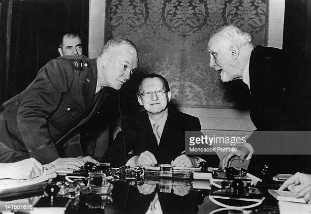 The Italian President of the Council Alcide De Gasperi sitting at a desk with General Dwight Eisenhower head of the US Armed Forces and the Minister...