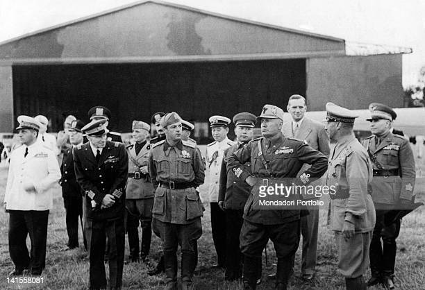 The Italian Prime Minister Benito Mussolini waiting for a flight coming from Tokyo with General Eraldo Ilari Colonel Giuseppe Casero Head of the Air...