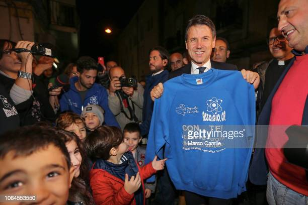 The Italian Prime Minister Giuseppe Conte visiting the Forcella district of Naples receives a tshirt dedicated to him by some children of the...