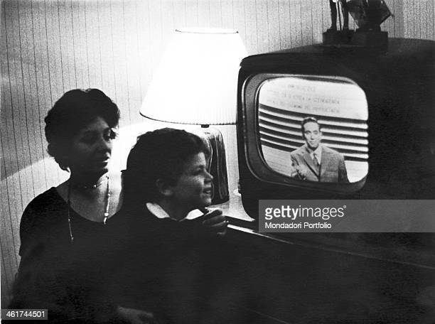 The Italian radio and television host Corrado Mantoni in a TV show his son Roberto is watching on TV and is smiling under the watchful eye of his...