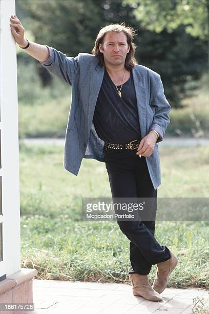 The Italian rock singer Vasco Rossi with his hand leaning against a wall crossed feet and a cigarette between his fingers Italy 1985