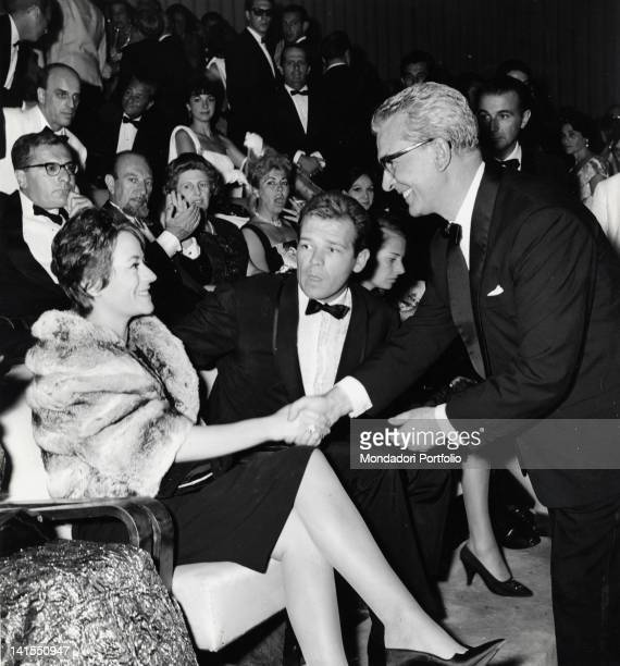 The Italian show director Domenico Meccoli shaking hands with Annie Girardot who won the Volpi Cup The French actress is accompanied by her husband...