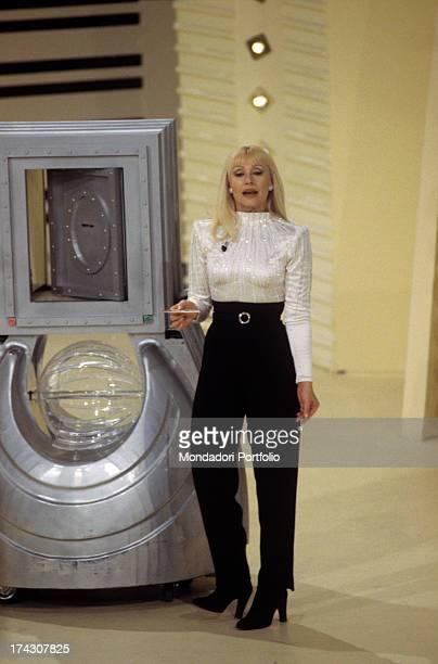 The Italian showgirl Raffaella Carrà born Raffaella Maria Roberta Pelloni stands beside the machinery for the lottery draw on the stage of the TV...