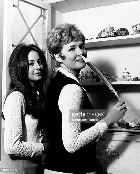 The Italian singer actress presenter show girl and impersonator Loretta Goggi is posing next to her younger sister Daniela and is keeping a quill in...