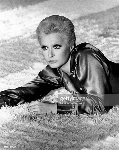 The Italian singer actress presenter show girl and impersonator Loretta Goggi is lying on a light coloured carpet and is wearing a dark shirt in...