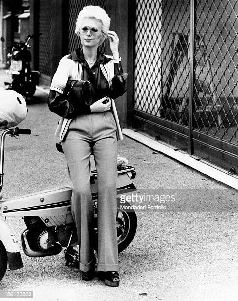 The Italian singer actress presenter show girl and impersonator Loretta Goggi is adjusting her hair while she is seated on a scooter which is parked...