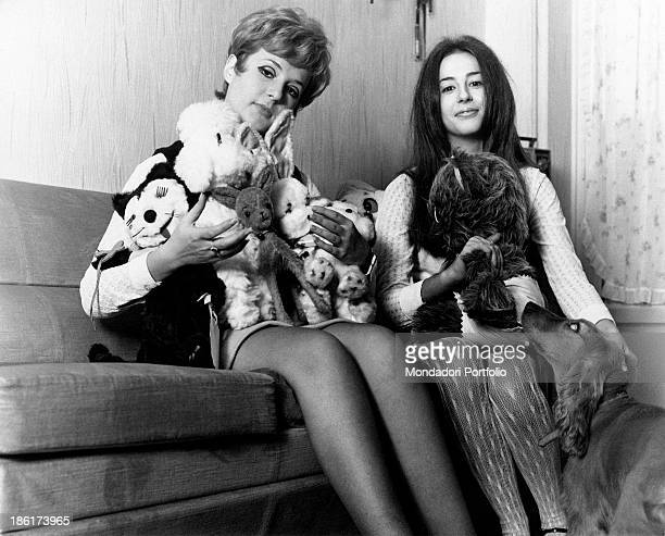The Italian singer actress presenter showgirl and impersonator Loretta Goggi is smiling next to her younger sister Daniela they are both seated on a...