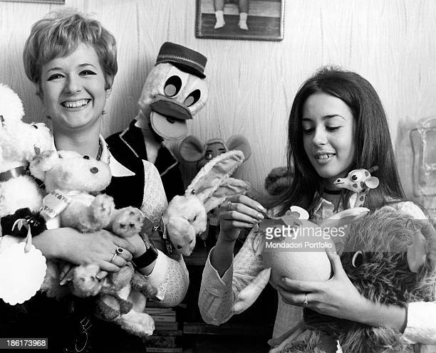 The Italian singer actress presenter showgirl and impersonator Loretta Goggi is smiling next to her younger sister Daniela they are keeping some...