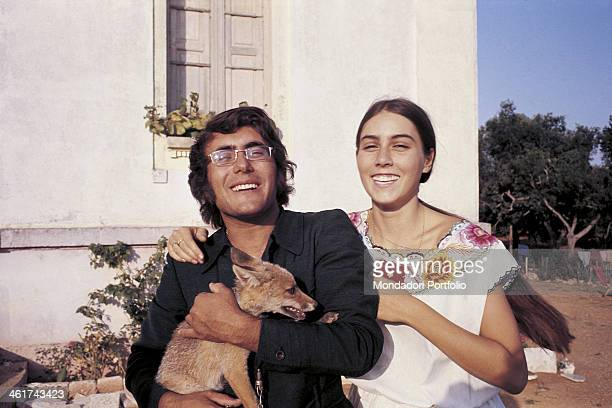 The italian singer Al Bano born Albano Carrisi smiles with his girlfriend Romina a Power and holds a dog Cellino SMarco Italy 1970