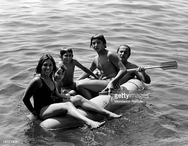 The Italian singer and actor Domenico Modugno transporting on a rubber dinghy his wife the Italian actress Franca Gandolfi and his sons Marco...