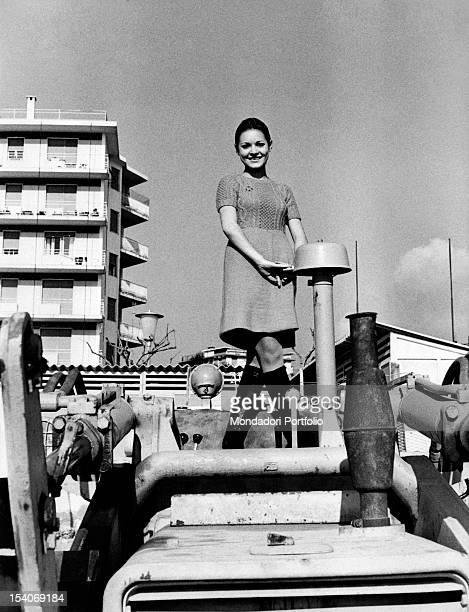 The Italian singer Anna Identici posing standing on an excavator Sanremo 1968