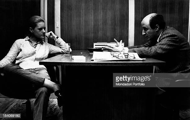 The Italian singer Anna Identici sitting at a writing desk with the Italian journalist Gigi Vesigna 1968