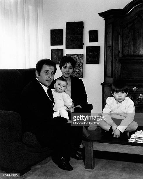 The italian singer Domenico Modugno together with his son Marco in their new home in Rome the artist is seated in an armchair and holds his son in...