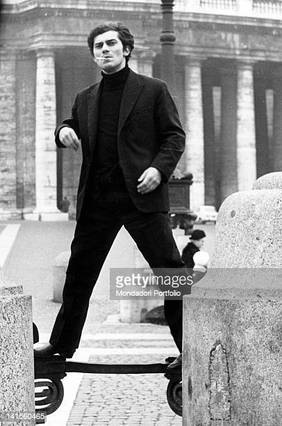 The Italian singer Luigi Tenco is standing on a wrought iron balustrade in San Pietro square State of the Vatican 1967