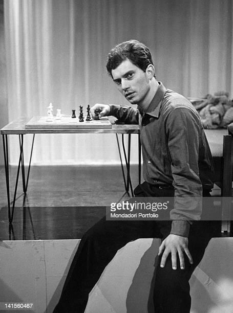 The Italian singer Luigi Tenco sitting beside a chessboard during a RAI tv show Italy
