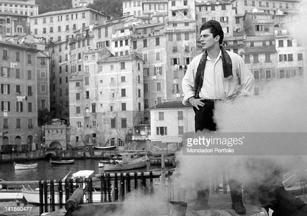 The Italian singer Luigi Tenco standing on the marina dock Camogli 1964