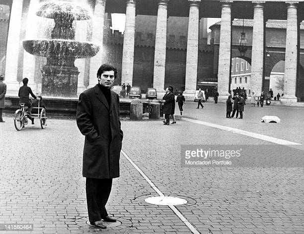 The Italian singer Luigi Tenco with his hands in pockets standing in San Pietro square. State of the Vatican, 1967