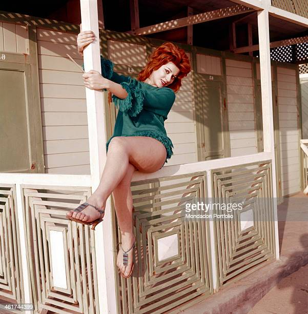 The Italian singer Miranda Martino is posing with crossed legs on a wooden fence with her arms clinging to a stake in a bathing establishment the...