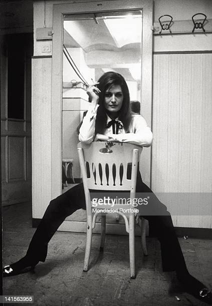 The Italian singer, naturalised French, Dalida poses on a chair at the XVII edition of Sanremo Italian Music Festival, where she sings the song 'Ciao...
