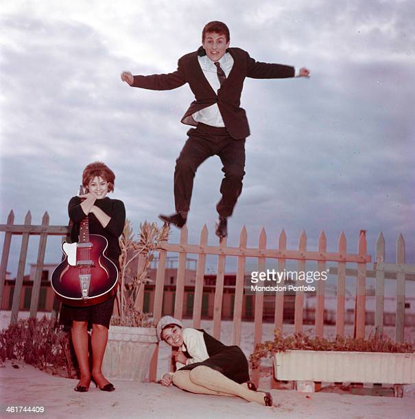 The Italian singer Tony Renis, born Elio Cesari, is jumping on a wooden fence on a beach in Sanremo; the Italian actress Laura Efrikian is curling up...
