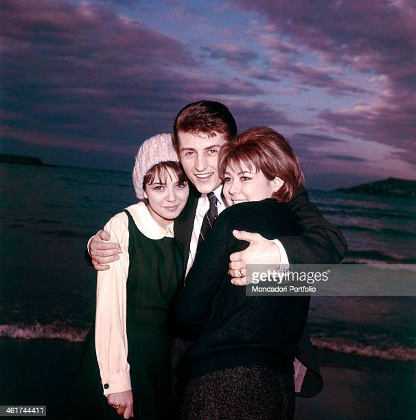 The Italian singer Tony Renis, born Elio Cesari, is smiling while embracing the Italian actresses Vicky Ludovisi and Laura Efrikian by the sea; in...
