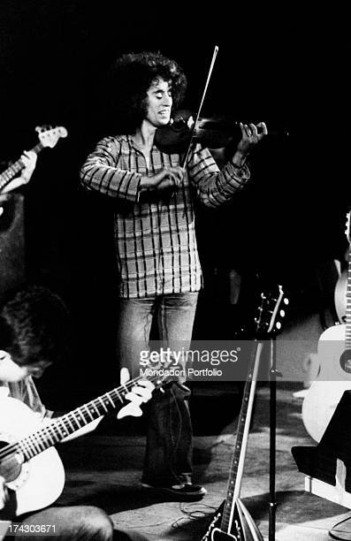 The Italian singersongwriter Angelo Branduardi plays the violin standing on stage during a performance Italy 1977
