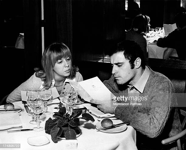 The Italian singersongwriter Edoardo Vianello and his first wife Wilma Goich an Italian singer are seated at the table and read the menu 1970