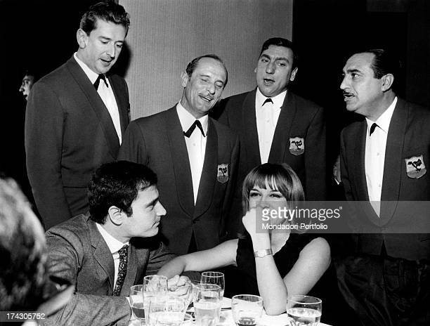 The Italian singersongwriter Edoardo Vianello is seated at a table with his wife Wilma Goich an Italian singer they are listening to a singing...