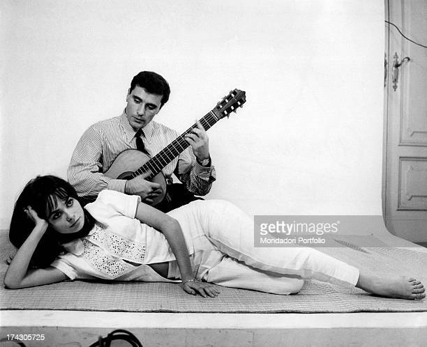 The Italian singersongwriter Edoardo Vianello poses holding a guitar in his hands with the Italian actress and singer Marisa Solinas who lies down on...