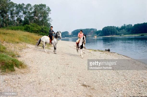 The Italian singersongwriter Lucio Battisti and the Italian lyricist Mogol are riding their horses along the bank of a river Battisti and Mogol are...
