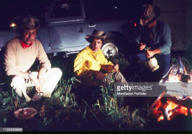 The Italian singersongwriter Lucio Battisti and the Italian lyricist Mogol in a moment of rest while eating dinner in front of a fire with another...