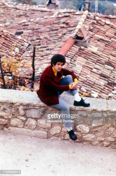 The Italian singersongwriter Lucio Battisti in his hometown sitting on a wall Poggio Bustone January 1969
