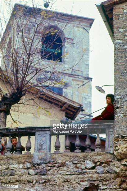 The Italian singersongwriter Lucio Battisti in his hometown sitting on a balustrade near a bell tower Poggio Bustone January 1969