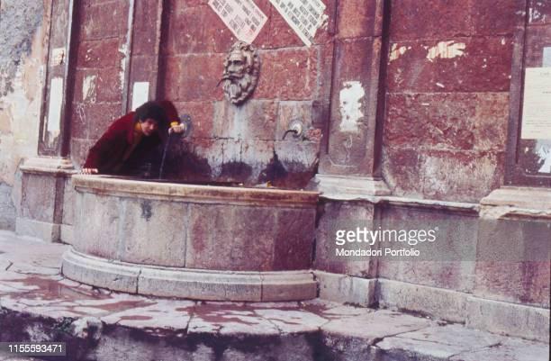 The Italian singersongwriter Lucio Battisti in his hometown while drinking at a fountain Poggio Bustone January 1969