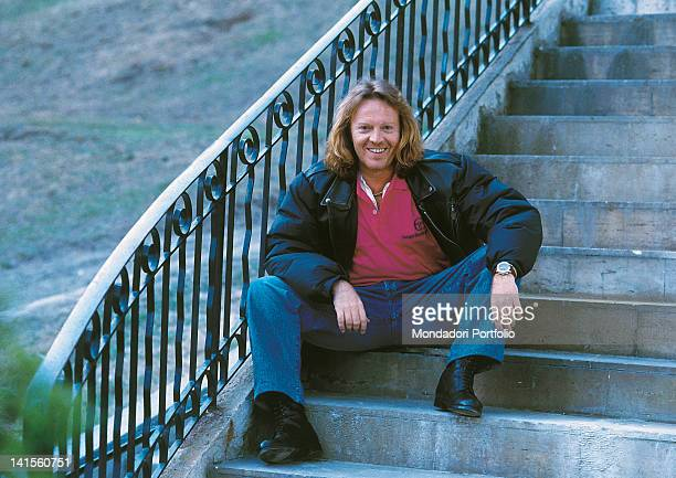 The Italian singer-songwriter Umberto Tozzi posing and smiling sat on a staircase. 1991