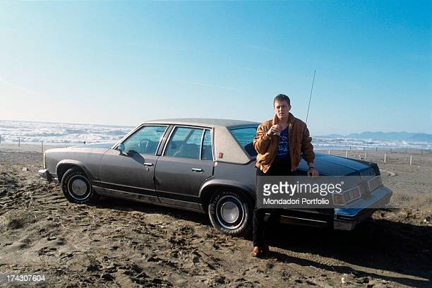 the Italian singersongwriter Zucchero Adelmo Fornaciari's pseudonym leans against a car on the beach Italy 1985