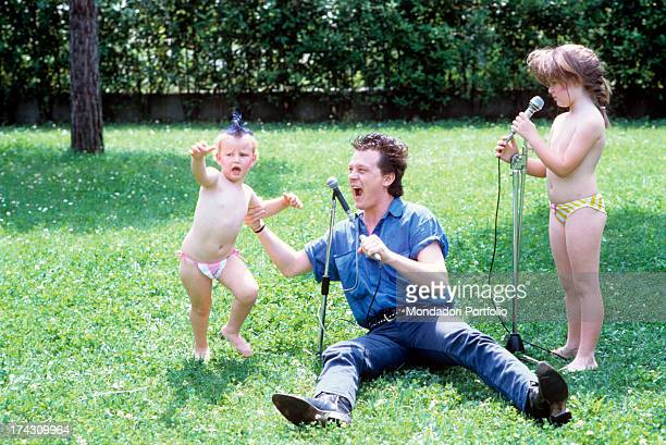 the Italian singersongwriter Zucchero born Adelmo Fornaciari poses in a garden seated on the grass between his daughters Irene and Alice Italy 1986
