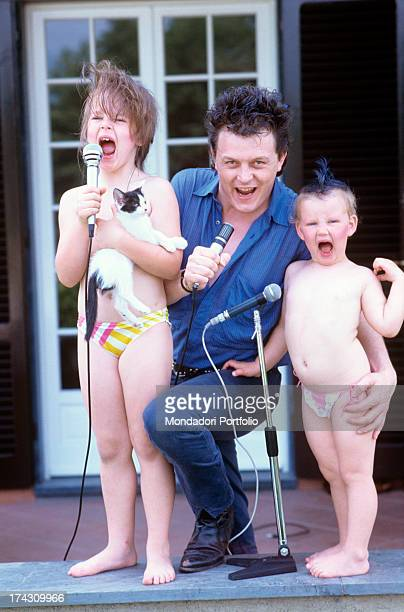 The Italian singersongwriter Zucchero born Adelmo Fornaciari poses singing out loud with his daughters Irene and Alice Italy 1986