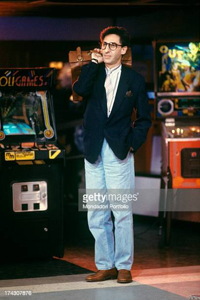 The Italian songwriter and singer from Sicily Francesco Battiato known as Franco Battiato is smiling in front of some videogames he is carrying a...