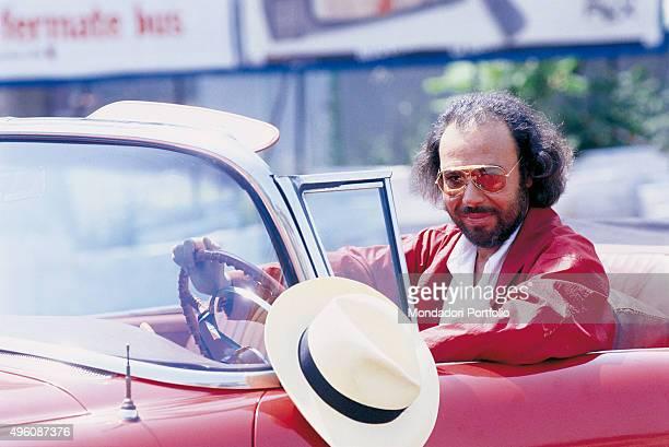 The Italian songwriter Antonello Venditti at the wheel of a red American vintage convertible car Photo shoot for the album Centro Città Rome 1985