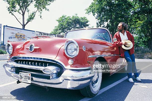 The Italian songwriter Antonello Venditti leaning on the car door of a red American vintage convertible car Photo shoot for the album Centro Città...