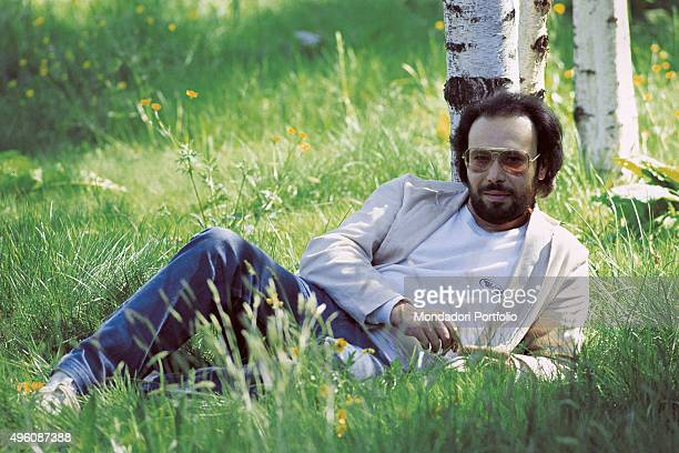 The Italian songwriter Antonello Venditti lying on a meadow during a photo shoot Italy 1982