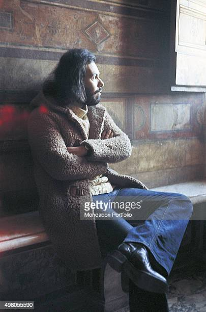 The Italian songwriter Antonello Venditti posing crossed arms on a bench looking out of a window Photo shoot Italy 1972