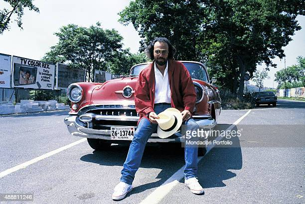 The Italian songwriter Antonello Venditti posing seated on the bumper of a red American vintage convertible car Photo shoot for the album Centro...