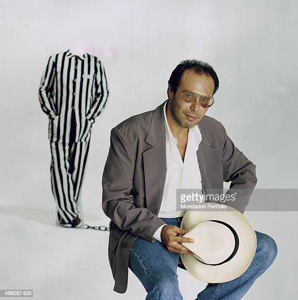 The Italian songwriter Antonello Venditti posing seated with a hat in his hand during a photo shoot realized for the album In questo mondo di ladri...