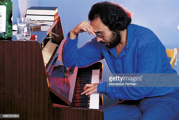 The Italian songwriter Antonello Venditti sitting in profile while playing a piano Italy 1984