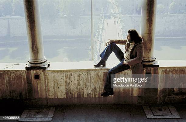 The Italian songwriter Antonello Venditti sitting under a loggia with his back leaning against a column Photo shoot Italy 1972