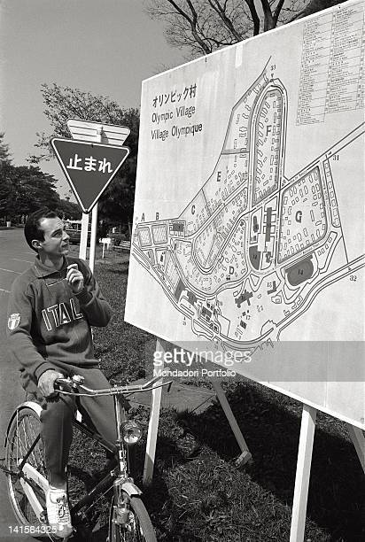 The Italian sprinter Livio Berruti on a bicycle looking at the Olympic Village poster. Japan, October 1964